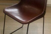 Siete sillas de hierro y cuero marrón.